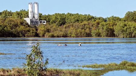 A wetland ecosystem typically flooded by water with abundant bird and fish life, with an industrial cement works in the background Stock Photo