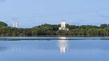 A cement works business on the banks of a wetlands ecosystem at sunset, with its reflection shining in the water Stock Photo