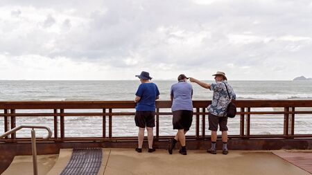 Yeppoon, Queensland, Australia - December 2019: Three holidaymakers watching the stormy sea at full tide, with the male retiree pointing towards and object he is talking about Editorial