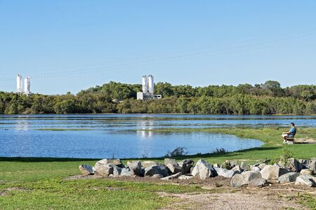 Mackay, Queensland, Australia - December 2019: Man sitting fishing and relaxing beside a wetlands ecosystem, with a factory in the background