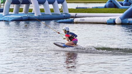 Mackay, Queensland, Australia - January 2020: A child wearing a safety helmet and life jacket enjoying a ride on a kneeboard at a cable park
