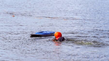 Child wearing a helmet for safety falls off a kneeboard at a wake park and swims back towards it