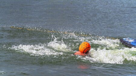 Child wearing a helmet for safety falls off a kneeboard at a cable park Reklamní fotografie