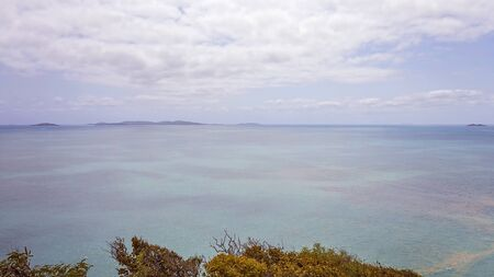 Trees in the foreground, with view out to Coral Sea from Bluff Point on the Capricorn Coast of Australia