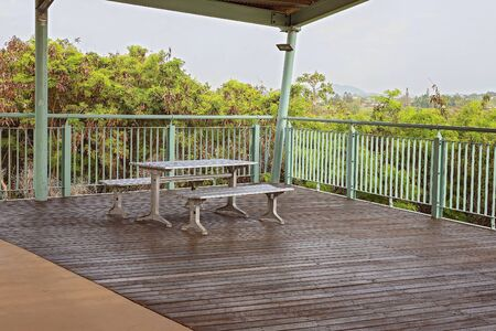 A covered timber deck with dining table and seating