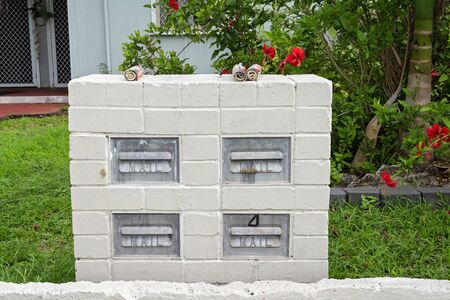 Four retro brick mail boxes in a garden