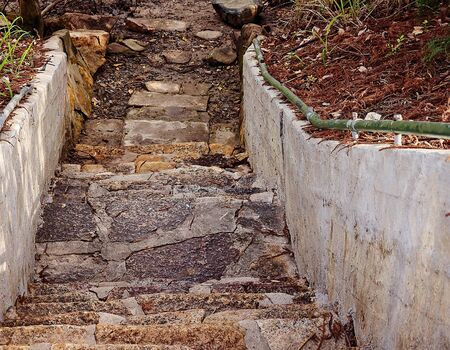 Old broken stone steps down onto a muddy track