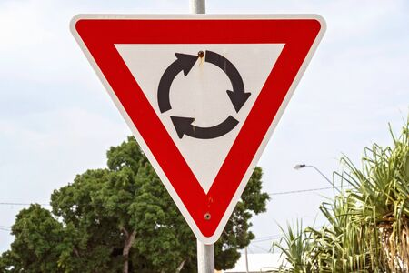 Signe de rond-point rouge et blanc avec des flèches noires