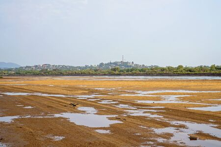 A river at low tide with water pooled in the sand