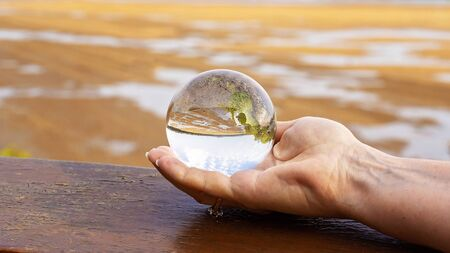 A glass lens ball held in the palm of a hand reflecting the river at low tide in the background