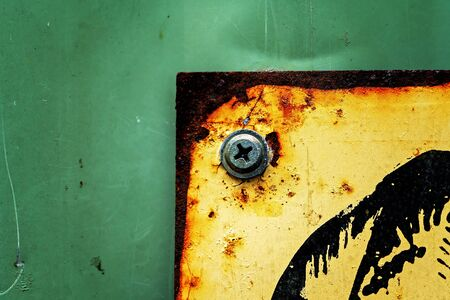 Part of an old yellow sign screwed onto a green metal background, full of abstract texture