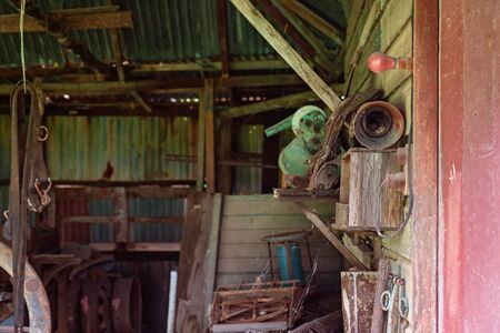 Old rusted farm tools from yesteryear in an abandoned country shed Foto de archivo