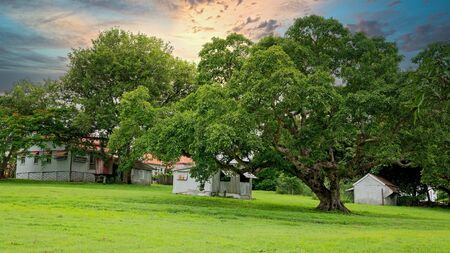 Sunset over an historic homestead set in parkland amongst lush green grass Stockfoto