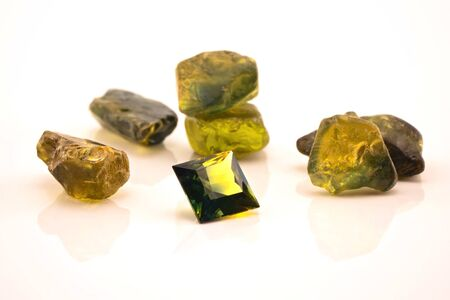 One square facet cut yellow green sapphire surrounded with uncut natural sapphires, isolated on a white background Stock Photo