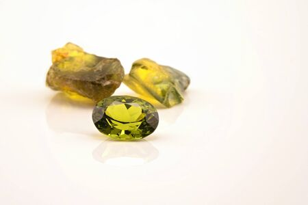 One oblong facet cut yellow green sapphire with two uncut natural sapphires of a similar colour, isolated on a white background