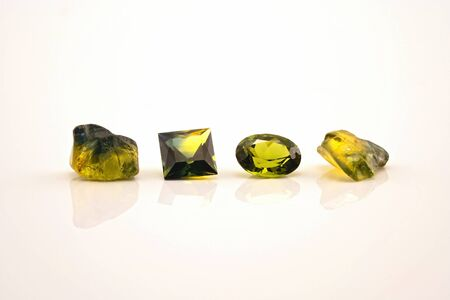 Two facet cut yellow green sapphire with two uncut natural sapphires of a similar colour, isolated on a white background