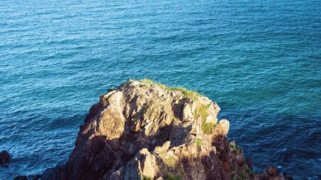 Looking down onto a rocky coastal outcrop on the ocean in late afternoon light