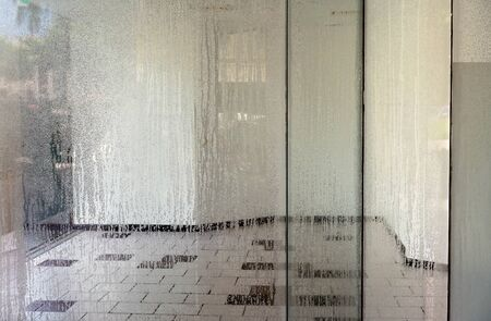 Humidity from hot weather streaking the glass of a vacant downtown shop Standard-Bild