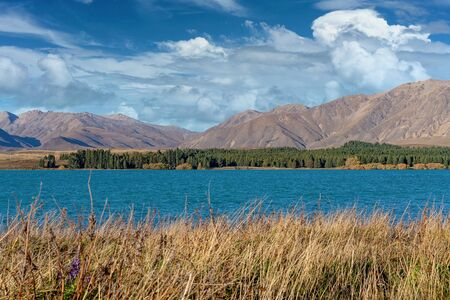 The azure blue water of Lake Tekapo in New Zealand under a cloudy sky