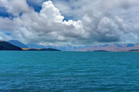 The azure blue water of Lake Tekapo in New Zealand under a cloudy sky Stock Photo