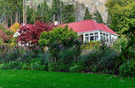 Lush autumn garden with colourful foliage in front of an red roofed cottage