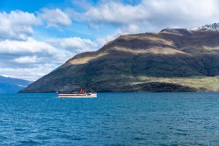 Steamship sailing from Queenstown on Lake Wakatipu in New Zealand against a mountain backdrop