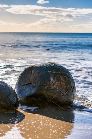 The round shapes of the Moeraki boulders dotted along this stretch of Otago coast in New Zealand