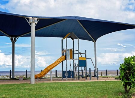 A beachfront shaded childrens playground with climbing frame and slipper slide