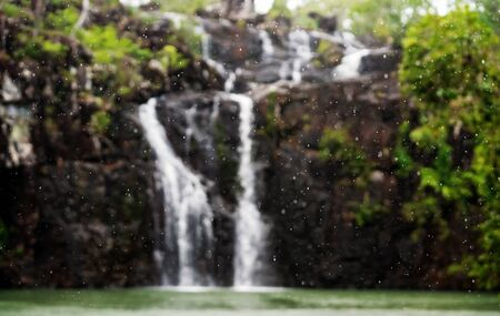 Rain drops falling in front of an intentionally blurred Cedar Creek Falls in North Queensland in the wet season