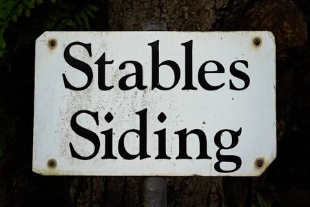Stables Siding retro metal sign on a steel post under a shady tree