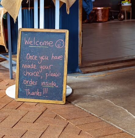 A welcome blackboard sign at a casual outdoor cafe with instructions to order inside