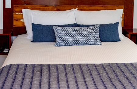 A freshly made up bed with clean linen and decorative pillows ready for occupancy