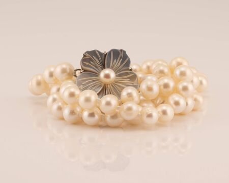 A string of lustrously glowing pearls designed as a necklace with a flower clasp, isolated on a white background Stock Photo