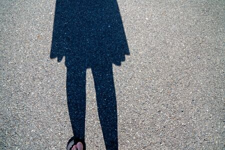 Shadow of a woman walking on a bitumen road