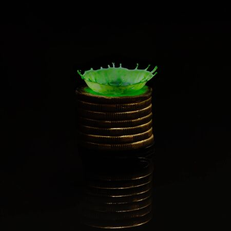 A green drop of milk splashed onto a stack of one dollar coins creates a crown shape with a water reflection against a black background