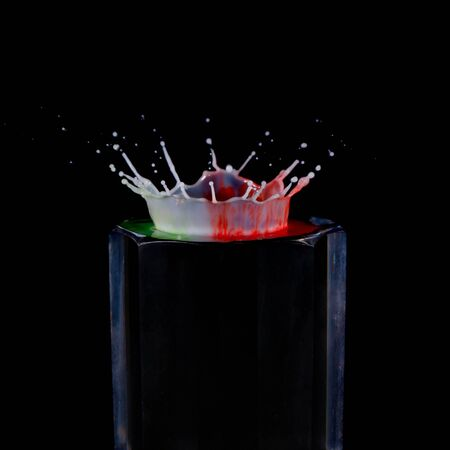 A drop of milk splashed onto pinpoints of color painted onto a wine decanter stopper creates a crown shape against a black background
