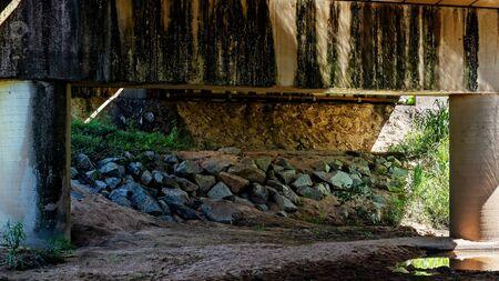 Underneath a highway concrete bridge over a creek bank Stock fotó