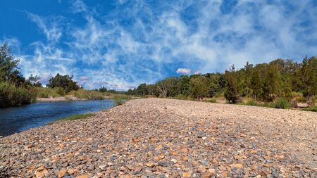 A dry and stony creek bed in the Australian countryside under a beautiful blue cloudy sky Imagens