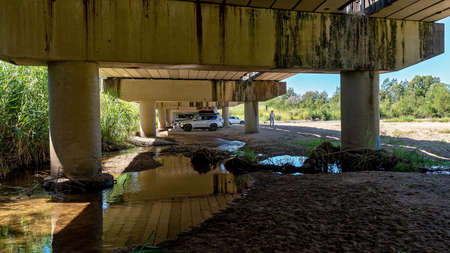 Mackay, Queensland, Australia - May 2020: A family in their car having a picnic in the shade under a bridge on a hot summer da