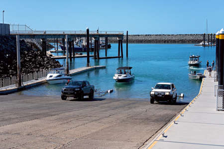Mackay, Queensland, Australia - June 2020: One fisherman launching his boat to go fishing and loading to go home, at public recreational ramp at marina