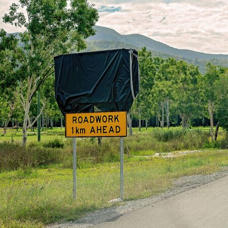 Upper sign covered up with lower one indicated there is roadwork happening 1 km ahead on the highway