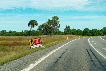 Prepare to stop sign on a country highway warning not to overtake other vehicles