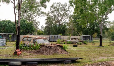 Old rusty cars planted in the garden of a country backyard acreage