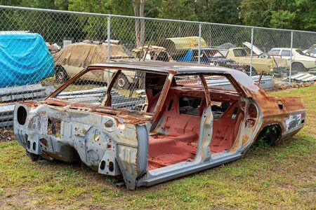 Part of the rusted frame of a classic car which was undergoing restoration but is now abandoned