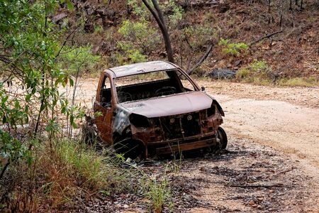 A burnt out car wreck abandoned on the side of a dirt mountain track