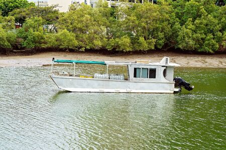 A vintage aluminium tin boat barge with modern outboard motor anchored on the river with its cargo
