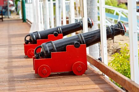 Small black canons in red carts at a public maritime museum Foto de archivo