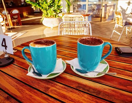 Cappuccinos on the outdoor terrace of a luxury hotel in early morning sunlight Stock Photo