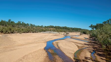 Water lying in sand on a dry outback Australian creek bed under a clear blue sky 写真素材