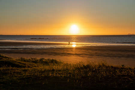 The orange sun rising brightly over the horizon on coastal Australia as two unidentifiable people run on the beach 스톡 콘텐츠
